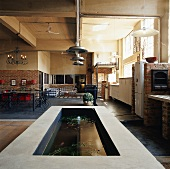 Gemauerter Fischteich im renouvierten Lagerhaus mit Backsteinelementen und Betondecke
