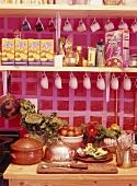 Lebensmittel, Tassen und Verpackungen im Regal über Arbeitsplatte mit Gemüse