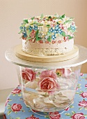 Glass bowl of roses with cake on top