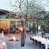 Festlich gedeckter Tisch unter freiem Himmel vor offenes Holzhaus im asiatischen Stil