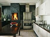Schlichte Vintage Küchenzeile und ein Edelstahlgasherd vor einer Tafelwand mit Kamin