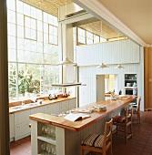 Elegante Vintageküche in einem aussergewöhnlichen Loft mit großen Industriefenstern und Terrakottaboden