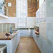 Blick in eine hellblaue Hochglanzküche mit hohem Sprossenfenster und Backsteinwänden