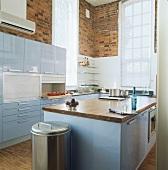 Moderne Küche mit hellblauen Hochglanzfronten und Backsteinwänden