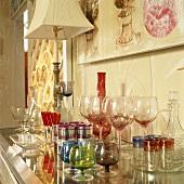 Gläser und Karaffen in verschiedenen Farben und Stilen auf einer Glaskommode