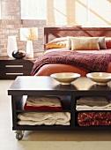 Moderner Ablagetisch auf Rollen am Fußende eines Bettes