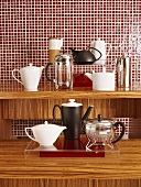 Various coffeepots and teapots on wooden surface in front of red mosaic wall tiles