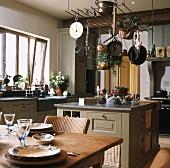 Rustikale Landhausküche mit Kochinsel unter hängenden Kochutensilien
