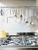 Gas hob and kitchen utensils hung on wall