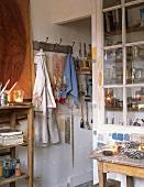 Atelier mit Vitrinenschrank, einfachem Holzregal und vielen Malutensilien