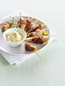 Bacon-wrapped pear wedges on cocktail sticks, cheese dip