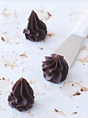 Three chocolate truffles piped using a star nozzle