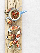 Steamed mussels with salsa topping on a plank of wood