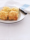 Four golden brown herb and cheese scones on a plate