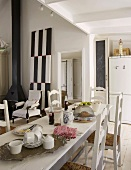 Set, white dining table and white rush-bottom chairs; black wood-burner and black and white artwork in background