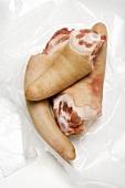 Three pigs' tails on plastic wrap