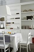 Weisses Esszimmer mit Einbauschrank und einem gedeckten Esstisch