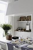Esszimmerausschnitt mit weißem Einbauschrank, gedecktem Tisch und mit Blick auf das Fenster