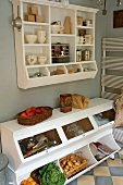 A kitchen floor cupboard with a wall-mounted shelf