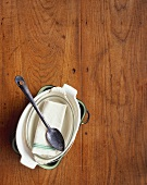 Baking dishes and spoon on wooden background