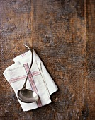 Ladle and tea towel on wooden background