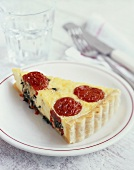 A piece of goat's cheese and tomato quiche with basil