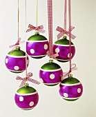 Several colourful Christmas baubles hanging on ribbons