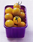 Yellow cocktail tomatoes in purple plastic container