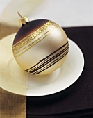 A brown and gold Christmas bauble (table decoration)