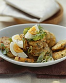 Bacon dumpling salad with spring onions and egg