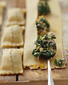 Filling pasta squares with spinach and ceps