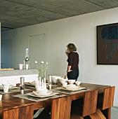 Frau trinkt in Wohnküche Kaffee, gedeckter Esstisch im Vordergrund
