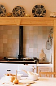 Wood oven in kitchen below china plates on wooden shelf