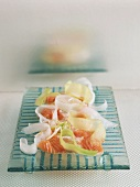 Marinated salmon with cucumber and courgette on a glass plate
