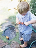 Little boy playing with garden hose