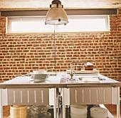Ein Küchenblock mit Edelstahloberfläche vor einer Backsteinwand mit breitem Oberlicht