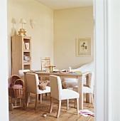 Rund um den schlichten, hellen Holztisch wird gebastelt, gemalt und gespielt