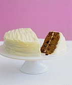 Carrot cake, a piece cut, on cake stand