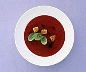 Red berry soup with croutons, balsamic vinegar & basil leaves