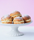 Yeast buns filled with vanilla cream on a cake stand