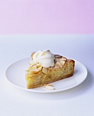 A piece of apple and almond tart with whipped cream