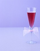 A glass of red sparkling wine cocktail with bow on glass