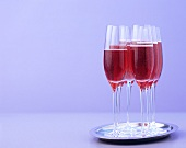 Several glasses of red sparkling wine cocktail on a tray