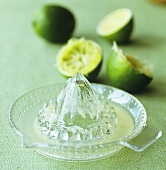 Lime juice in citrus squeezer and squeezed limes
