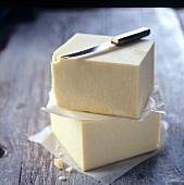Zwei Stücke Cheddar mit Käsemesser