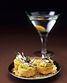 Small guacamole tarts, glass of Martini