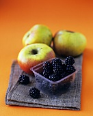 A punnet of blackberries and three apples