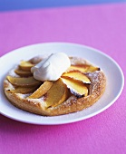 Small peach tart with cream on plate