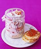 Crabmeat in dill cream sauce in storage jar, blinis