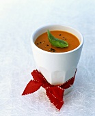 Cream of tomato soup in beaker with red bow
